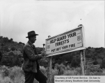 Ranger Grant G. Williams nailing up fire prevention sign