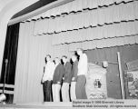 Five men performing on stage at Cedar High School