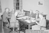 Unidentified men sitting around a table