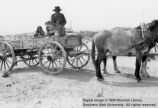 Man and two children on wagon; Cameron, Arizona