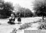 Randle Lunt and boy on horseback riding through flood waters; Cedar City, Iron County, Utah