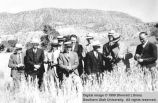 Elders standing in wheat at edge of field; Cedar City, Iron County, Utah