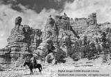 Man on horse by large rock wall at Bryce Canyon